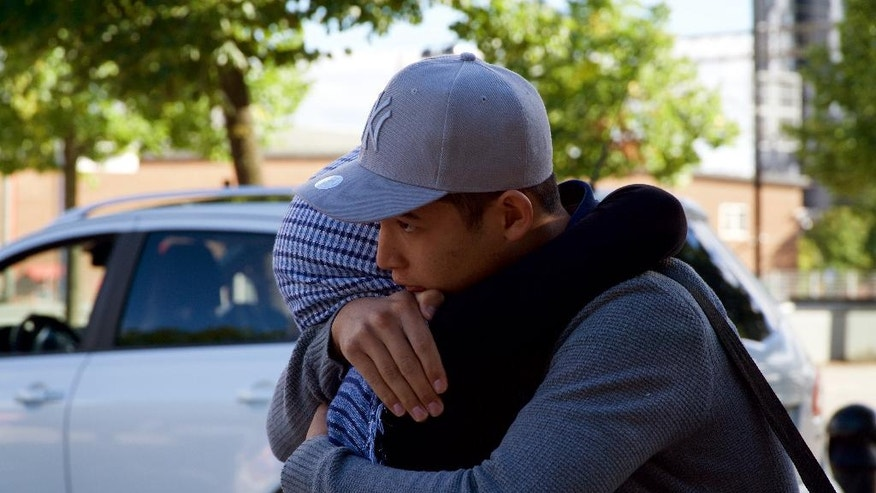 In this Aug. 14, 2016 photo, Mahdi Azizi hugs his mother goodbye before boarding a bus to return to a centre for unaccompanied minors, in Vasteras, Sweden. Love, not war, made the Azizi family flee Iran during last summer's chaotic mass migration to Europe. Luck reunited them a year after a dark night in a Turkish forest separated 14-year-old Mahdi Azizi from his parents and sisters. (AP Photo/David Keyton)
