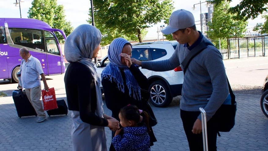 In this Aug. 14, 2016 photo, Mahdi Azizi wipes a tear from his mother's eye prior to him boarding a bus to return to a centre for unaccompanied minors, in Vasteras, Sweden. Love, not war, made the Azizi family flee Iran during last summer's chaotic mass migration to Europe. Luck reunited them a year after a dark night in a Turkish forest separated 14-year-old Mahdi Azizi from his parents and sisters. (AP Photo/David Keyton)