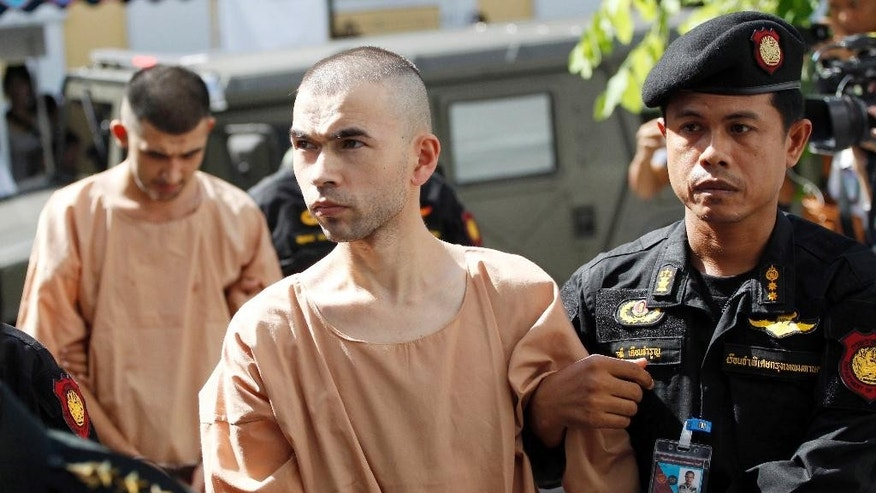 FILE - In this Nov. 24, 2015 file photo, police officers escort suspects in the Aug. 17 blast at Erawan Shrine, Bilal Mohammad, front, and Mieraili Yusufu, rear, as they arrive at a military court in Bangkok, Thailand. A Thai military court on Tuesday, Aug. 23, 2016 began the trial of two foreigners charged with the bombing of a popular shrine in Bangkok's center a year ago that killed 20 people and injured more than 120. (AP Photo/Sakchai Lalit, File)