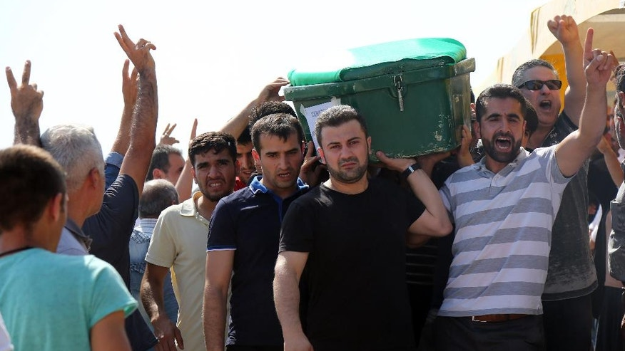 """People carry a victim's coffin as they attend funeral services for dozens of people killed in last night's bomb attack targeting an outdoor wedding party in Gaziantep, southeastern Turkey, Sunday, Aug. 21, 2016. Deputy Prime Minister Mehmet Simsek said the """"barbaric"""" attack in Gaziantep, near the border with Syria, on Saturday appeared to be a suicide bombing. Turkish authorities have put a temporary ban on distribution of images relating to Saturday's Gaziantep attack within Turkey.(AP Photo/Mahmut Bozarslan)"""