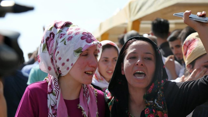 """People mourn as they attend funeral services for dozens of people killed in last night's bomb attack targeting an outdoor wedding party in Gaziantep, southeastern Turkey, Sunday, Aug. 21, 2016. Deputy Prime Minister Mehmet Simsek said the """"barbaric"""" attack in Gaziantep, near the border with Syria, on Saturday appeared to be a suicide bombing. Turkish authorities have put a temporary ban on distribution of images relating to Saturday's Gaziantep attack within Turkey.(AP Photo/Mahmut Bozarslan)"""