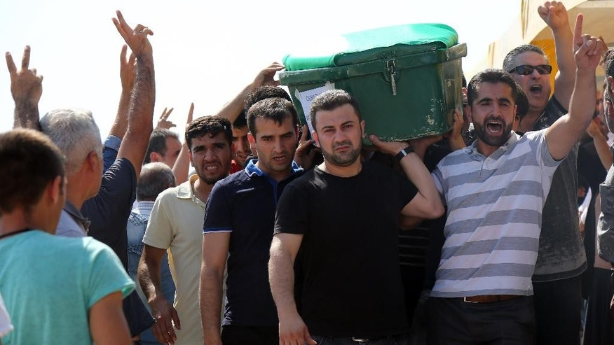"People carry a victim's coffin as they attend funeral services for dozens of people killed in last night's bomb attack targeting an outdoor wedding party in Gaziantep, southeastern Turkey, Sunday, Aug. 21, 2016. Deputy Prime Minister Mehmet Simsek said the ""barbaric"" attack in Gaziantep, near the border with Syria, on Saturday appeared to be a suicide bombing. Turkish authorities have put a temporary ban on distribution of images relating to Saturday's Gaziantep attack within Turkey.(AP Photo/Mahmut Bozarslan)"
