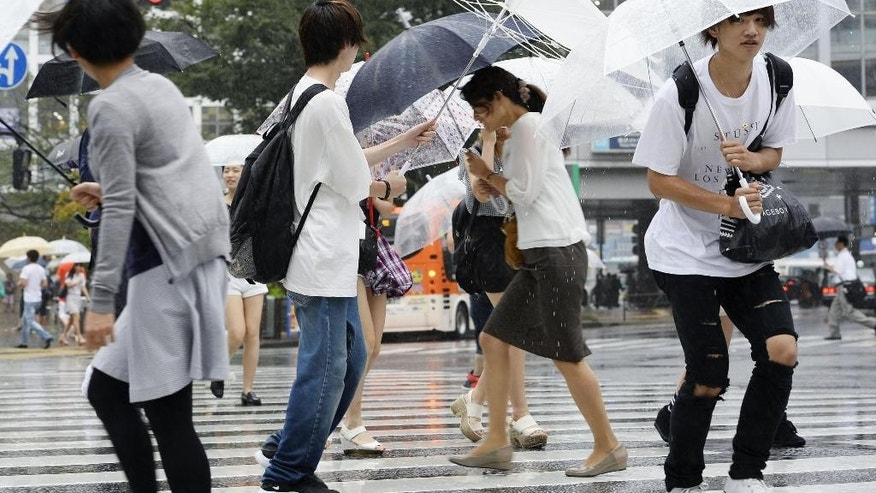 People walk in a strong wind caused by Typhoon Mindulle, in Tokyo Monday, Aug. 22, 2016. The typhoon sweeping through Tokyo and surrounding areas has forced the cancellation of more than 400 domestic flights in Japan and disrupted train service. (Akiko Matsushita/Kyodo News via AP)