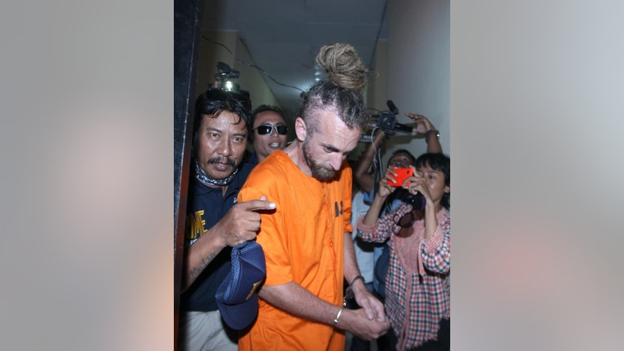 Indonesian police officers escort murder suspect David Taylor, center, to an investigator's room at a local police station in Bali, Indonesia, Tuesday, Aug. 23, 2016. Indonesian police have arrested an Australian woman and a British man in connection with the alleged murder of a police officer in the tourist resort of Bali. (AP Photo/Firdia Lisnawati)