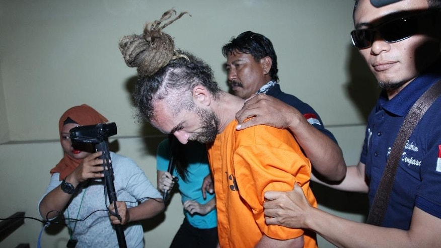 Indonesian police officers escort murder suspect David Taylor, second from right, to an investigator's room at a local police station in Bali, Indonesia, Tuesday, Aug. 23, 2016. Indonesian police have arrested an Australian woman and a British man in connection with the alleged murder of a police officer in the tourist resort of Bali. (AP Photo/Firdia Lisnawati)