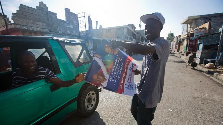 A supporter of Maryse Narcisse gives out campaign posters promoting the presidential candidate, in Port-au-Prince, Haiti, Tuesday, Aug. 23, 2016. Campaign season begins yet again for Haiti as authorities organize a redo of last year's presidential vote. ( AP Photo/Dieu Nalio Chery)