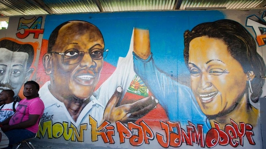 "A mural that decorates a wall features Haiti's former President Jean Bertrand Aristide and presidential candidate Maryse Narcisse with a message that reads in Creole; ""People who won't obey"" in response to foreigners suggesting how the country's politics should be run, in Port-au-Prince, Haiti, Tuesday, Aug. 23, 2016. Campaign season begins yet again for Haiti as authorities organize a redo of last year's presidential vote.  (AP Photo/Dieu Nalio Chery)"