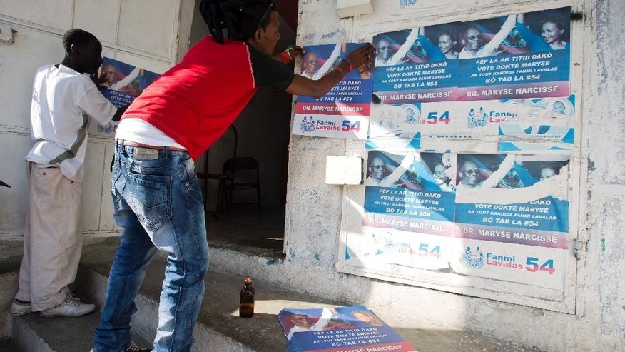 Supporters of Maryse Narcisse post campaign posters promoting the presidential candidate in downtown of Port-au-Prince, Haiti, Tuesday, Aug. 23, 2016. Campaign season begins yet again for Haiti as authorities organize a redo of last year's presidential vote. (AP Photo/Dieu Nalio Chery)