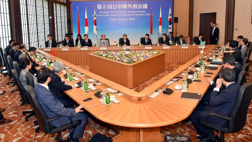 Japanese Foreign Minister Fumio Kishida, center in the background, makes opening remark during a trilateral meeting in Tokyo, Wednesday, Aug. 24, 2016. The foreign ministers of China, Japan and South Korea have criticized North Korea's fresh missile launch just hours earlier in the day. (Katsumi Kasahara/Pool Photo via AP)