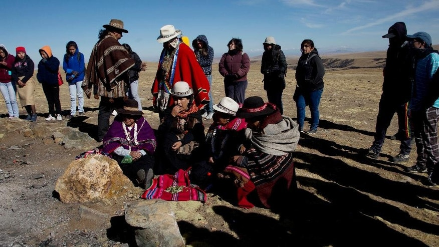 In this Aug. 13, 2016 photo, Aymara priests chew coca leaves before the start of a ceremony in honor of Pachamama or Mother Earth, on the outskirts of El Alto, Bolivia. According to Andean mythology, Pachamama awakens every August hungry and thirsty after the Bolivian dry season. To satiate the goddess, believers hold syncretic rituals in which they toss offerings including fruit, coca, sweets and a dead llama fetus into a bonfire and they water the soil with the warm blood of a sacrificed llama. (AP Photo/Juan Karita)
