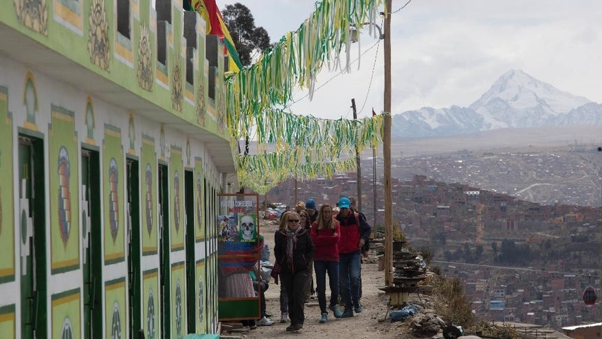 In this Saturday, Aug. 19, 2016 photo, foreign tourists walk on their way to see a ceremony in honor of Pachamama or Mother Earth, at La Ceja in El Alto, Bolivia. The tour starting in El Alto goes to four sites and last five hours. Prices vary but it includes bus transportation, refreshments and a spiritual cleansing by women clenching fistfuls of herbs. (AP Photo/Juan Karita)