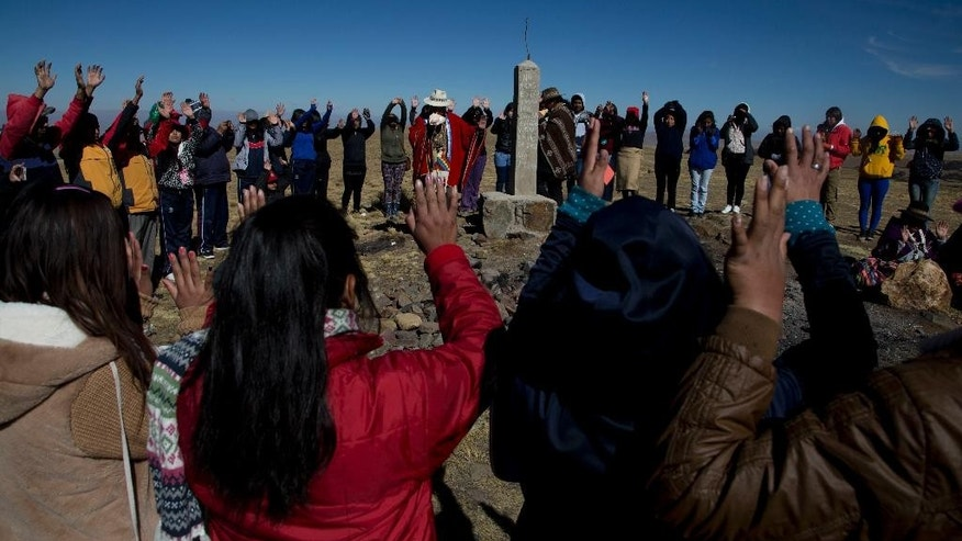 In this Aug. 13, 2016 photo, an Aymara priest leads a prayer before the start of a ceremony in honor of Pachamama or Mother Earth, during a tour at a scared site on the outskirts of El Alto, Bolivia. Officials are in the early stages of creating the first dedicated tours of sacred sites of the Pachamama. They're especially targeting foreign visitors, whose numbers are growing, said Diego del Carpio, head of tourism for the city. (AP Photo/Juan Karita)
