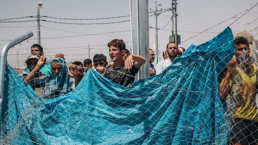 In this August 17, 2016 photo, men wait outside a fenced area at the Dibaga Camp for displaced people, where newcomers are interrogated before being allowed to stay, in Hajj Ali, northern Iraq. As the Islamic State group loses ground in Iraq, the militants are showing strains in their rule over areas they still control, growing more brutal, executing deserters and relying on younger recruits, according to residents. The accounts pointed to the difficulties the extremist group is facing as Iraqi forces backed by the United States prepare for an assault on Mosul. (AP Photo/Alice Martins)