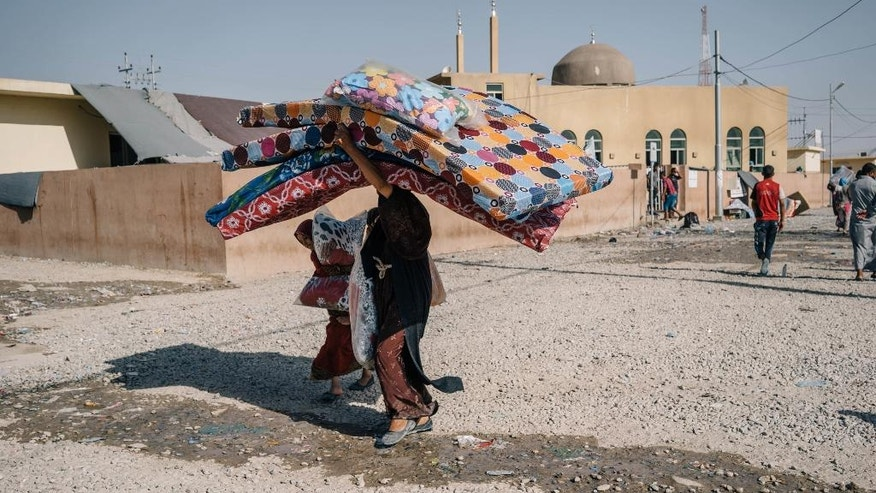 In this Aug. 17, 2016 photo, a woman and a girl walk past a mosque carrying mattresses and cushions at the Dibaga Camp for displaced people, in Hajj Ali, northern Iraq. As the Islamic State group loses ground in Iraq, the militants are showing strains in their rule over areas they still control, growing more brutal, executing deserters and relying on younger recruits, according to residents. The accounts pointed to the difficulties the extremist group is facing as Iraqi forces backed by the United States prepare for an assault on Mosul. (AP Photo/Alice Martins)