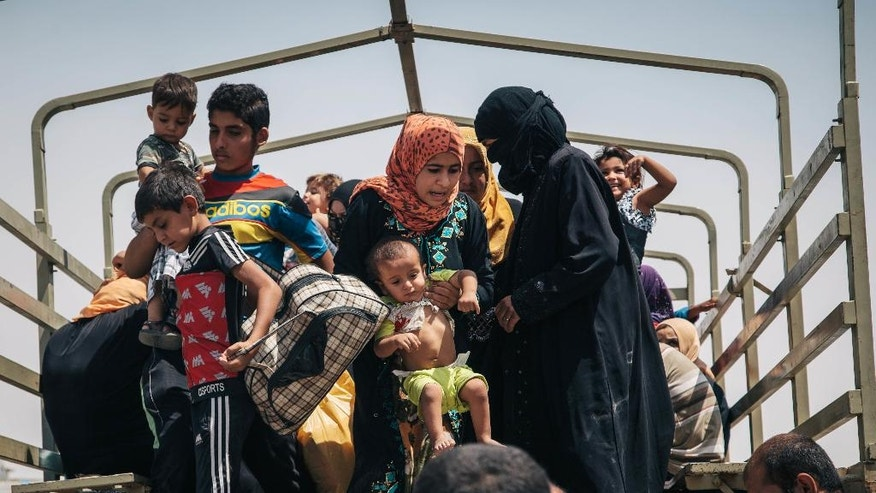In this Aug. 17, 2016 photo, civilians who recently fled territory formerly controlled by Islamic State militants get off a truck at the Dibaga Camp for displaced people in Hajj Ali, northern Iraq. As the Islamic State group loses ground in Iraq, the militants are showing strains in their rule over areas they still control, growing more brutal, executing deserters and relying on younger recruits, according to residents. The accounts pointed to the difficulties the extremist group is facing as Iraqi forces backed by the United States prepare for an assault on Mosul. (AP Photo/Alice Martins)