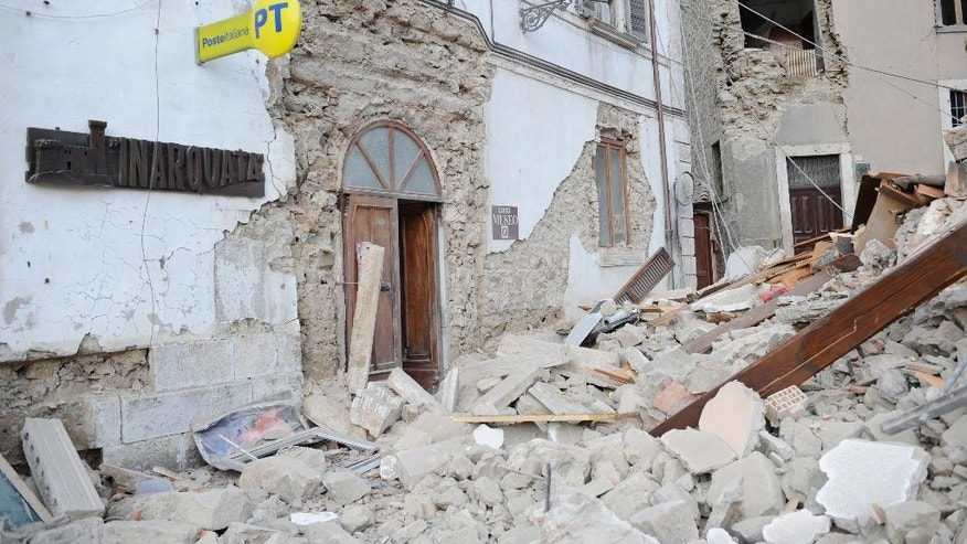 A post office is engulfed by rubbles in Arcuata del Tronto, central Italy, where a 6.1 earthquake struck just after 3:30 a.m., Wednesday, Aug. 24, 2016. The quake was felt across a broad section of central Italy, including the capital Rome where people in homes in the historic center felt a long swaying followed by aftershocks. (AP Photo/Sandro Perozzi)