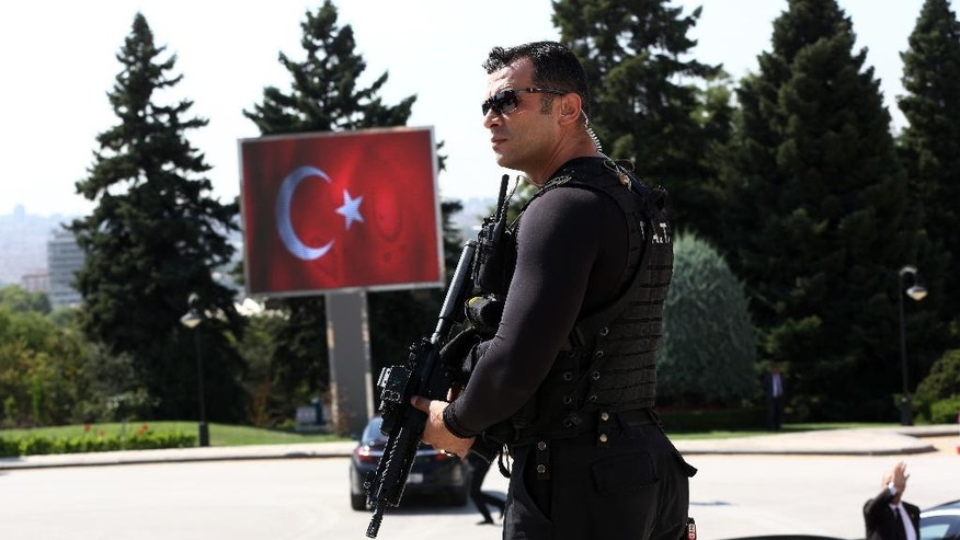A Special Security force member on guard at the mausoleum of Turkey's founder Kemal Ataturk as Turkish Prime Minister Binali Yildirim, military commanders and ministers visit the mausoleum to pay respects, in Ankara, Turkey, Tuesday, Aug. 23, 2016. Turkish media reports say Turkish artillery on Tuesday launched new strikes at Islamic State targets across the border in Syria, after two mortar rounds, believed to have been fired by the militants, hit the town of Karkamis, in Turkey's Gaziantep province. Hurriyet newspaper and other reports said the mortar rounds were fired from IS-held Jarablus, Syria.(AP Photo/Burhan Ozbilici)
