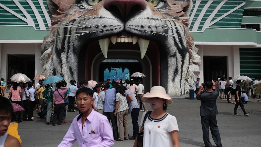 North Koreans wait at the gate of the newly opened Pyongyang Central Zoo in Pyongyang, North Korea, Tuesday, Aug. 23, 2016. North Korean leader Kim Jong Un's latest gift to the lucky residents of Pyongyang, the renovated central zoo, is pulling in thousands of visitors a day with a slew of attractions ranging from such typical zoo fare as elephants, giraffes, penguins and monkeys to a high-tech natural history museum. (AP Photo/Dita Alangkara)