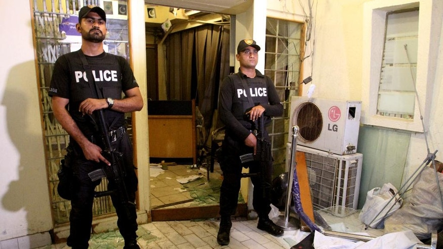 Pakistani police commandos stand guard in local media office, after an attack by supporters of Pakistan's Muttahida Qaumi Movement in Karachi, Pakistan, Monday, Aug. 22, 2016. Pakistani officials say protesters have attacked TV stations and clashed with police in the southern city of Karachi, leaving one person dead and eight others wounded, including three media workers. (AP Photo/Fareed Khan)