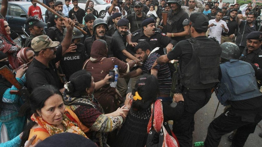 Activists of Pakistan's Muttahida Qaumi Movement clash with police in Karachi, Pakistan, Monday, Aug. 22, 2016. Pakistani officials say protesters have attacked TV stations and clashed with police in the southern city, leaving one person dead and eight others wounded, including three media workers. (AP Photo/Fareed Khan)