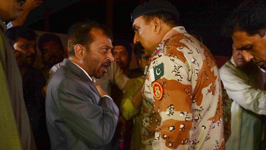 Farooq Sattar, left, leader of Pakistan's Muttahida Qaumi Movement argues with officer of Pakistan Rangers in Karachi, Pakistan, Monday, Aug. 22, 2016. Pakistani officials say protesters have attacked TV stations and clashed with police in the southern city of Karachi, leaving one person dead and eight others wounded, including three media workers. (AP Photo/Fareed Khan)