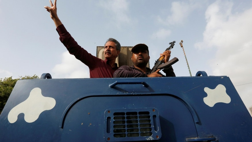 Waseem Akhtar, left, being taken to jail in July.