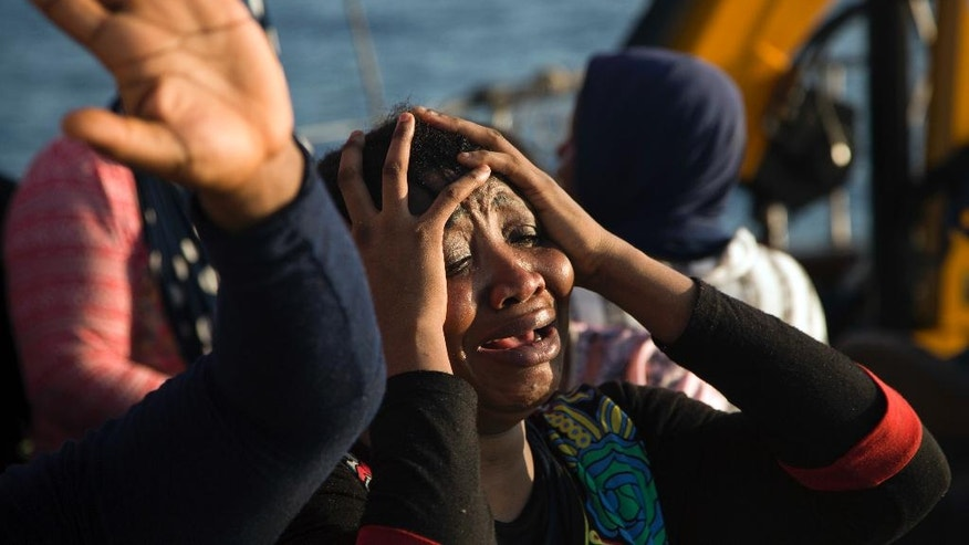 A woman from Nigeria reacts on the Astral vessel after been rescued by members of Proactiva Open Arms NGO, during a rescue operation at the Mediterranean sea, about 17 miles north of Sabratah, Libya, Saturday, Aug. 20, 2016. Migrants seemingly prefer to face the dangers of the journey towards Europe, rather than stay at home.(AP Photo/Emilio Morenatti)