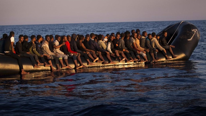 Migrants, mostly from Nigeria, crowd onto a dinghy as the sail fleeing Libya, before being helped by members of a Spanish NGO, during a rescue operation at the Mediterranean sea, about 17 miles north of Sabratah, Libya, Saturday, Aug. 20, 2016. Migrants seemingly prefer to face the dangers of the journey towards Europe, rather than stay at home.(AP Photo/Emilio Morenatti)