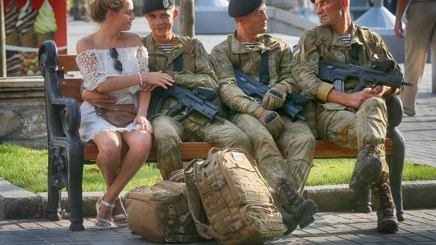 A soldier shares a tender moment with his girlfriend while other soldiers rest during a rehearsal of a military parade a few days before the Independence Day in Kiev, Ukraine, Monday, Aug. 22, 2016. Ukraine to mark the 25th anniversary of the Independence Day on Aug. 24. (AP Photo/Efrem Lukatsky)