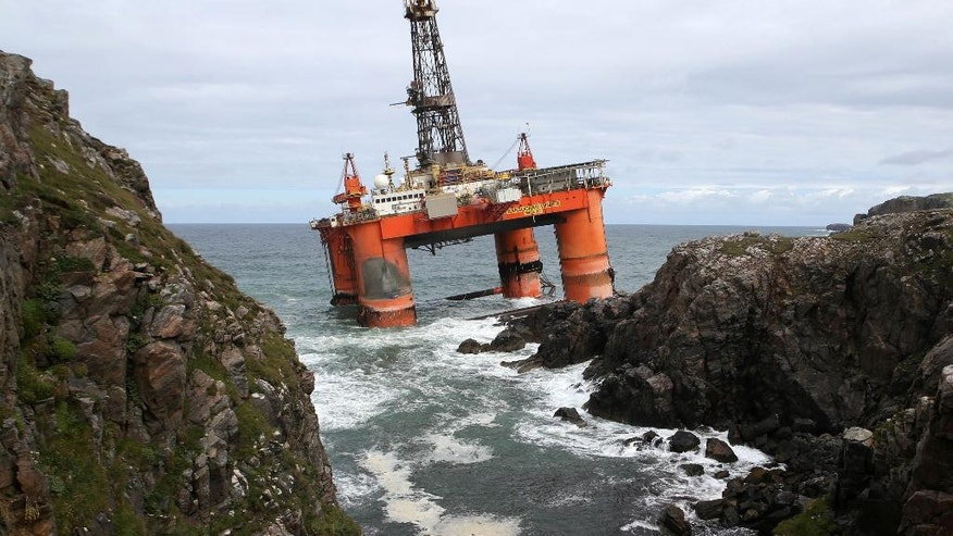 FILE - In this file photo dated Oct. 9, 2016, showing the Transocean Winner drilling rig as it broke free from tug boats in rough seas and ran aground off the Isle of Lewis, Outer Hebrides, Scotland.  Final preparations are being made for high tide on Monday Aug. 22, 2016, to re-float the 17,000-tonne oil rig carrying some 280 tons of diesel on board.  (Andrew Milligan / PA FILE via AP)