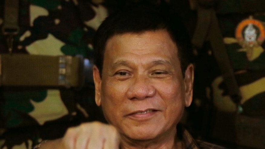 Philippine President Rodrigo Duterte gestures with a fist bump during his visit to the Philippine Army's Camp Mateo Capinpin at Tanay township, Rizal province east of Manila, Philippines Wednesday, Aug. 24, 2016. President Duterte's threat to withdraw the Philippines from the United Nations, later cushioned by his foreign secretary, is the latest flamboyantly irreverent utterance from a politician who has disparaged the pope, human rights advocates, the United States and other countries who controvert his worldview. (AP Photo/Bullit Marquez)
