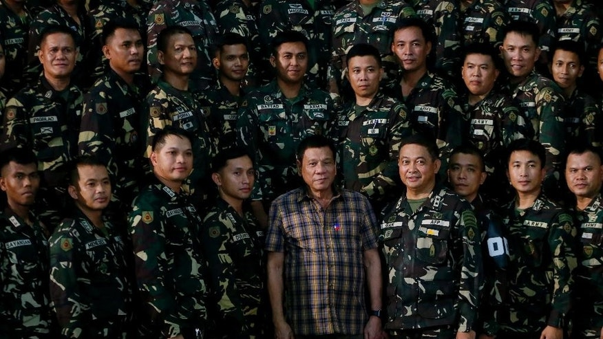 Philippine President Rodrigo Duterte poses with Philippine troops during his visit to the Philippine Army's Camp Mateo Capinpin at Tanay township, Rizal province east of Manila,Philippines Wednesday, Aug. 24, 2016. President Duterte's threat to withdraw the Philippines from the United Nations, later cushioned by his foreign secretary, is the latest flamboyantly irreverent utterance from a politician who has disparaged the pope, human rights advocates, the United States and other countries who controvert his worldview.(AP Photo/Bullit Marquez)