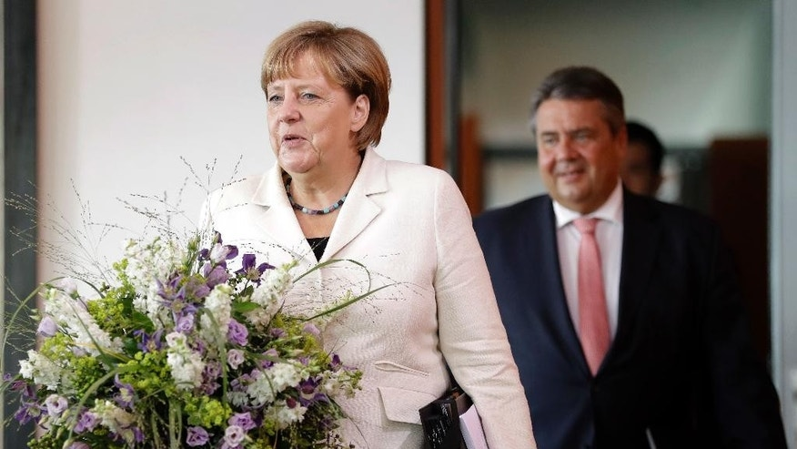 German Chancellor Angela Merkel, left, holds a bunch of flowers as a birthday present for a member of the cabinet during her arrival for the weekly cabinet meeting at the Chancellery in Berlin, Germany, Wednesday, Aug. 24, 2016. At right is German Minister for Economic Affairs and Energy Sigmar Gabriel. (AP Photo/Michael Sohn)