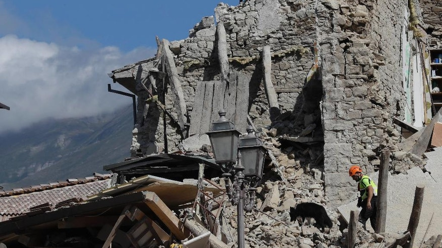 A rescuer walks a sniff dog as they search through the debris of collapsed houses following an earthquake in Amatrice, central Italy, Wednesday, Aug. 24, 2016. The magnitude 6 quake struck at 3:36 a.m. (0136 GMT) and was felt across a broad swath of central Italy, including Rome where residents of the capital felt a long swaying followed by aftershocks. (AP Photo/Alessandra Tarantino)