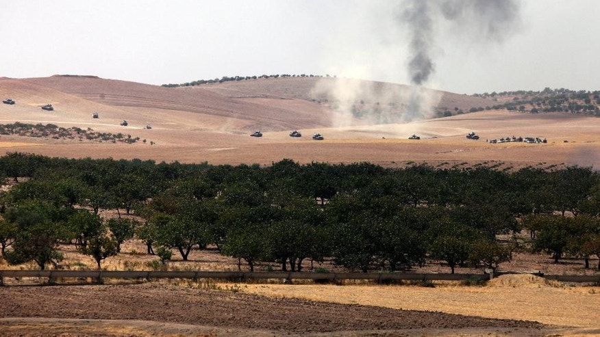 Turkish army tanks move toward the Syrian border as pictured from Karkamis, Turkey, Wednesday, Aug. 24, 2016. Turkey's military launched an operation before dawn Wednesday to clear a Syrian border town from Islamic State militants, and a private Turkish TV station reported that a small number of Turkish special forces had crossed into Syria as part of the operation. The operation was launched hours before Vice President Joe Biden was due in Ankara for talks that include developments in Syria.(AP Photo)