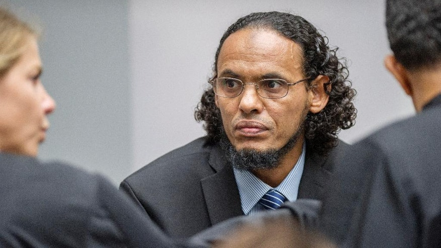 Ahmad Al Faqi Al Mahdi, center, appears at the International Criminal Court in The Hague, Netherlands, Monday Aug. 22, 2016, at the start of his trial on charges of involvement in the destruction of historic mausoleums in the Malian desert city of Timbuktu. Prosecutors allege that Al Mahdi was a member of an al Qaida-linked occupying force that destroyed most of Timbuktu's World Heritage-listed mausoleums in 2012. (AP Photo/Patrick Post, Pool)