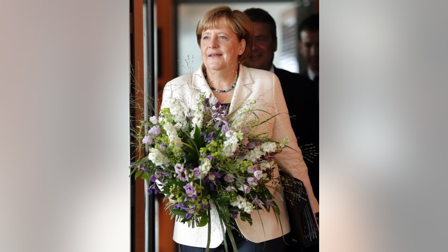 German Chancellor Angela Merkel holds a bunch of flowers as a birthday present for a member of the cabinet during her arrival for the weekly cabinet meeting at the Chancellery in Berlin, Germany, Wednesday, Aug. 24, 2016. (AP Photo/Michael Sohn)