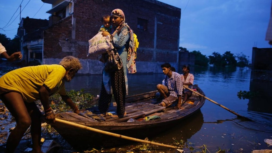 People leave for safer places due to the flooding in the river Ganges in Allahabad, India, Tuesday, Aug. 23, 2016. Days of heavy rain have caused the Ganges River and its tributaries to rise above the danger level during the past 48 hours in about 20 districts of the states of Madhya Pradesh, Bihar and Uttar Pradesh. (AP Photo/Rajesh Kumar Singh)