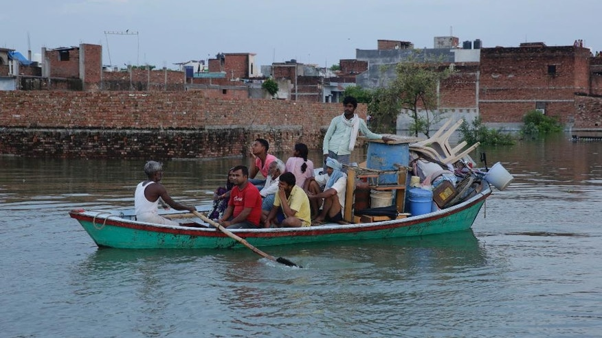 People leave for safer places with their belongings due to the flooding in the river Ganges in Allahabad, India, Tuesday, Aug. 23, 2016. Days of heavy rain have caused the Ganges River and its tributaries to rise above the danger level during the past 48 hours in about 20 districts of the states of Madhya Pradesh, Bihar and Uttar Pradesh. (AP Photo/Rajesh Kumar Singh)