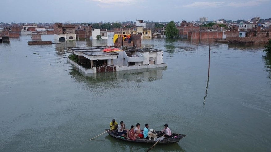 An Indian family with their pets return home with their pets after being away due to the flooding in the river Ganges in Allahabad, India, Tuesday, Aug. 23, 2016. Days of heavy rain have caused the Ganges River and its tributaries to rise above the danger level during the past 48 hours in about 20 districts of the states of Madhya Pradesh, Bihar and Uttar Pradesh. (AP Photo/Rajesh Kumar Singh)