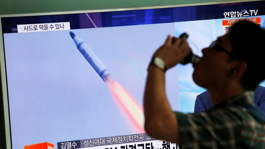 A passenger walks past a TV screen broadcasting a news report on North Korea's submarine-launched ballistic missile fired from North Korea's east coast port of Sinpo, at a train station in Seoul, South Korea.