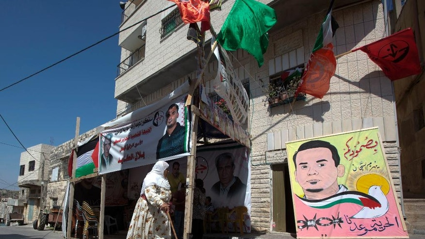 In this Saturday, Aug. 13, 2016 photo, Palestinian woman walks in front of a tent set up in solidarity with Bilal Kayed, 34, in front of his family home in the village of Assira al-Shamaliya near the West Bank city of Nablus. Attorney Sahar Francis said Bilal Kayed stopped his protest Wednesday after 71 days of fasting. Francis said there is an agreement that will see him freed in December. Kayed began the fast in June after Israel ordered him held for six months without charges, immediately following completion of a 14-and-a-half-year prison term, his relatives said. (AP Photo/Majdi Mohammed, File)