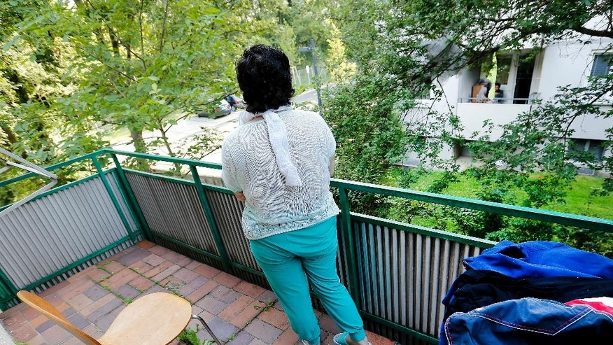 In this July 28, 2016 picture 17-year-old Yazidi girl stands on the balcony of her home in Germany.  After escaping the clutches of Islamic State, Yasmin, a  Yazidi girl, was so traumatized by her captivity that she poured gasoline on herself and set it alight -  hoping to render herself no longer desirable to the extremists. Two years later, she's being treated in Germany not only for her physical wounds, but for the psychological damage that led her to her act of desperation.  (AP Photo/Michael Probst)
