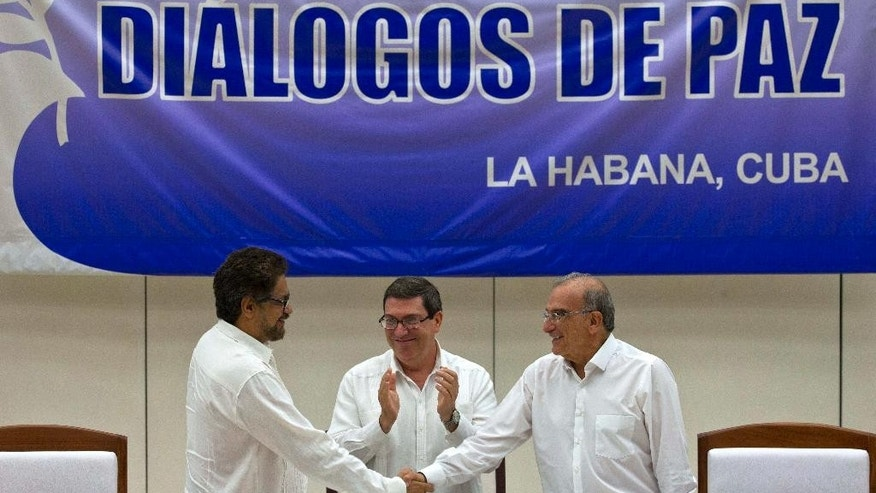 Humberto de la Calle, right, head of Colombia's government peace negotiation team, shakes hands with Ivan Marquez, chief negotiator of the Revolutionary Armed Forces of Colombia, left, while Cuban Foreign Minister Bruno Rodriguez, center, applauds after signing an agreement in Havana, Cuba, Wednesday, August 24, 2016. Colombia's government and the country's biggest rebel group reached a deal for ending a half-century of hostilities in what has been one of the world's longest-running armed conflicts.  (AP Photo/Ramon Espinosa)