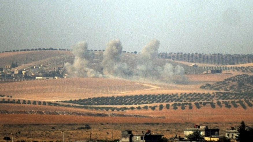 Smokes billow in Syrian side, pictured from Karkamis, Turkey, Wednesday, Aug. 24, 2016. Turkey's military and the U.S.-backed coalition forces on Wednesday launched an operation to clear a Syrian border town from Islamic State militants, Turkey's prime minister's office said. The state-run Anadolu Agency said the operation, which began hours after Turkey indicated it would step up its engagement in Syria, began at 4 a.m. with Turkish artillery launching intense fire on Jarablus from the Turkish town of Karkamis, followed by Turkish warplanes bombing IS targets in the town.(DHA via AP)