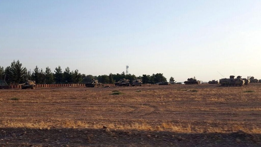 Turkish army tanks are stationed near the border with Syria, in Karkamis, Turkey, Tuesday, Aug. 23, 2016. Turkey's military and the U.S.-backed coalition forces on Wednesday, Aug. 24, 2016 launched an operation to clear a Syrian border town from Islamic State militants, Turkey's prime minister's office said. The state-run Anadolu Agency said the operation, which began hours after Turkey indicated it would step up its engagement in Syria, began at 4 a.m. with Turkish artillery launching intense fire on Jarablus from the Turkish town of Karkamis, followed by Turkish warplanes bombing IS targets in the town. (AP Photo)