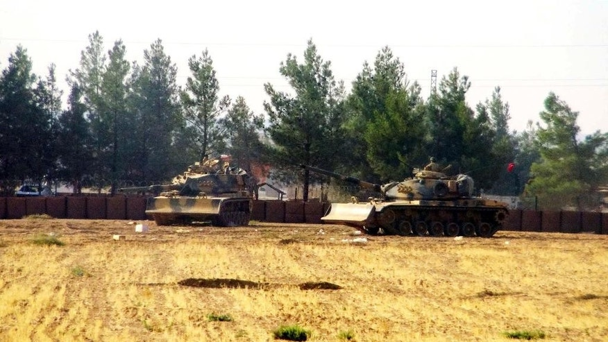 Turkish army tanks are stationed near the border with Syria, in Karkamis, Turkey, Wednesday, Aug. 24, 2016. Turkey's military launched an operation before dawn Wednesday to clear a Syrian border town from Islamic State militants, and a private Turkish TV station reported that a small number of Turkish special forces crossed into Syria as part of the operation. (DHA via AP)