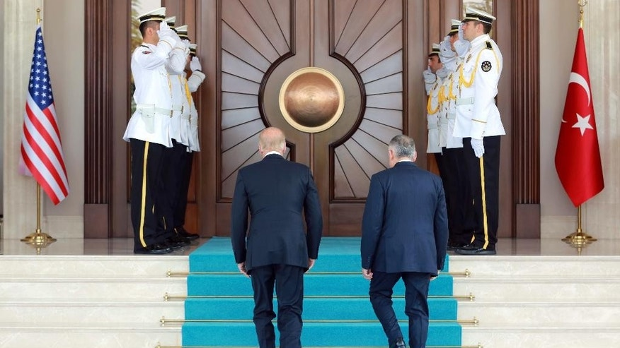 U.S Vice President Joe Biden, left, and Turkish Prime Minister Binali Yildirim walk to review a guard of honour before a meeting in Ankara, Turkey, Wednesday, Aug. 24, 2016. Biden has arrived in Ankara for talks with Turkish leaders as Turkey launched a military operation to clear a Syrian border town of Islamic State militants. The visit comes at a difficult time for ties between the two NATO allies.(AP Photo/Burhan Ozbilici)