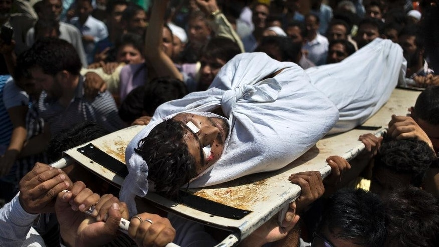Kashmiri Muslim men carry the body of Amir Mir outside a local hospital in Srinagar, Indian controlled Kashmir, Wednesday, Aug. 24, 2016. Mir died of pellet injuries as severe protests continued in the valley with tens of thousands of Indian armed police and paramilitary soldiers patrolling the tense region after the killing of a popular rebel commander on July 8 sparked some of Kashmir's largest protests against Indian rule in recent years. (AP Photo/Dar Yasin)