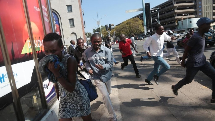 Protestors flee teargas in Harare Wednesday, Aug. 24, 2016 after Zimbabwe police fired tear gas, water cannons and gunshots to stop hundreds of youths protesting against police brutality. (AP Photo)